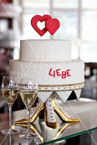 A two-tier wedding cake with red hearts and red writing on an unusual cake stand