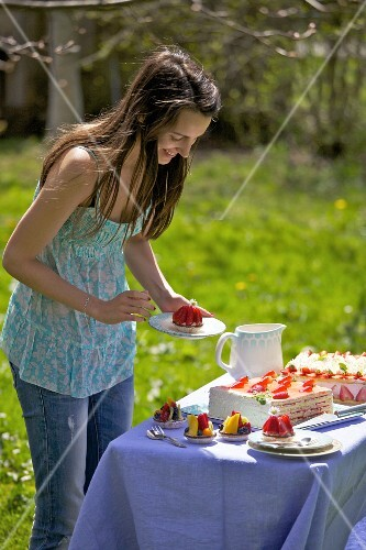 A young woman by a cake buffet outdoors