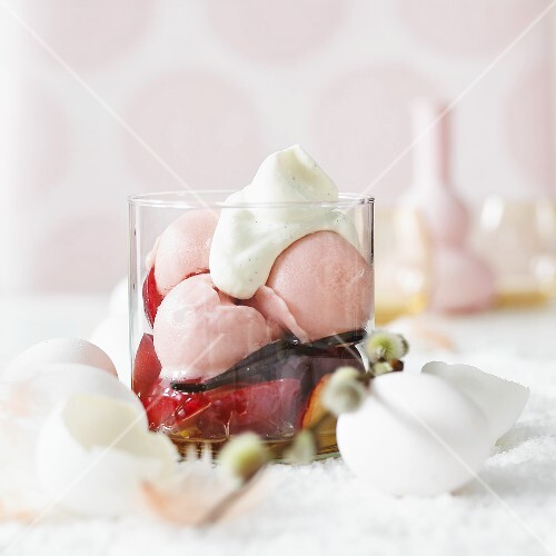 Fruit ice cream on marinated plums with vanilla pods and cream for Easter