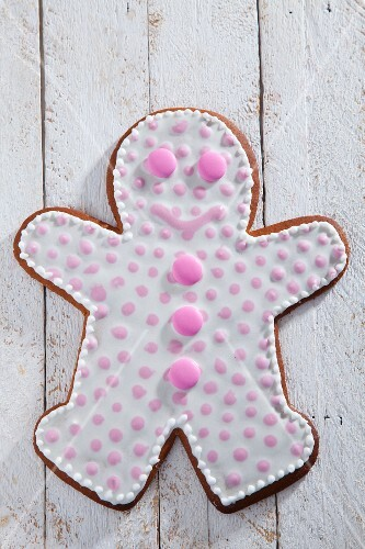 A gingerbread man decorated with pink dots