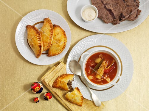 Borscht, served with meat pasties and a plate of sliced meat