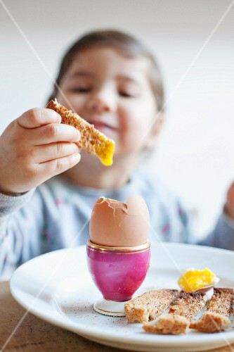 A girl dipping a toast soldier in a soft-boiled egg