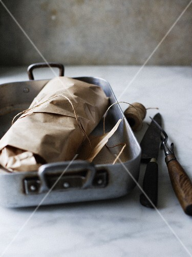 Meat wrapped in brown paper in a roasting tin with carvers and kitchen string