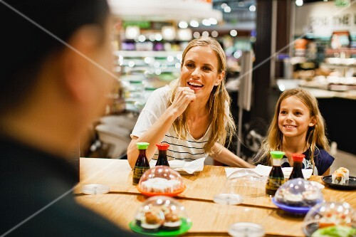 A mother and daughter eating sushi in a gourmet food shop