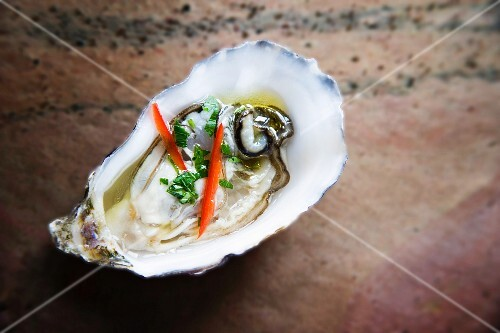 Oyster in half shell dressed with lime, chilli and coriander