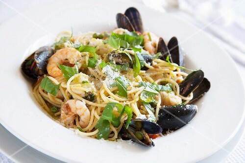 Cooked spaghetti, mussels, prawns and pieces of fish fillet