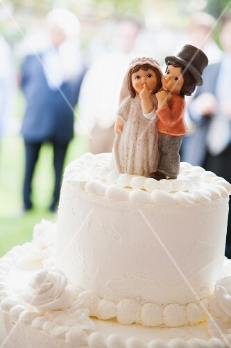 A white wedding cake with a sweet decorative bride and groom
