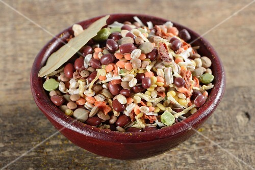 Pearl barley, green lentils, red lentils, aduki beans, mung beans, soup vegetables, bay leaf, onions and tomato flakes in a ceramic bowl