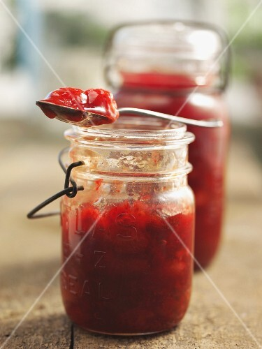 Strawberry jam in a jar and on a spoom