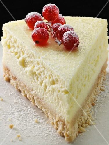 A piece of New York cheesecake with redcurrants