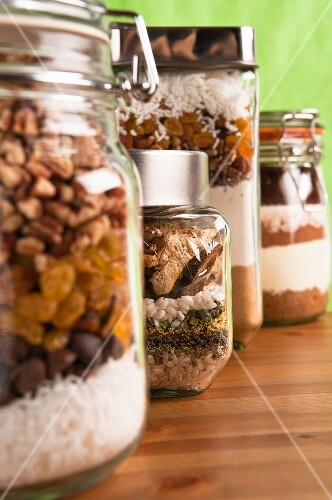 Four jars, containing dry ingredients for making coconut fruit slices, mushroom risotto, fruitcake and almond mocha