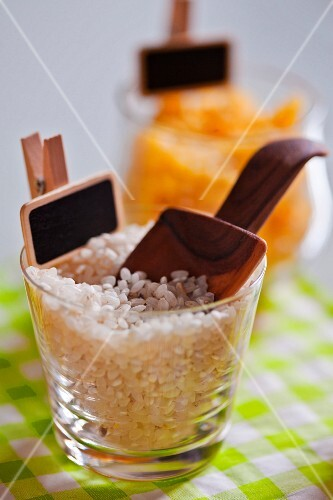 Short grain rice in a jar with a wooden scoop and a label