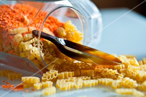 Dried pasta and red lentils in an overturned storage jar with a scoop