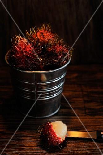 Several rambutans in a small metal bucket