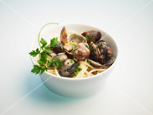 Spaghetti with clams in a bowl against a white background