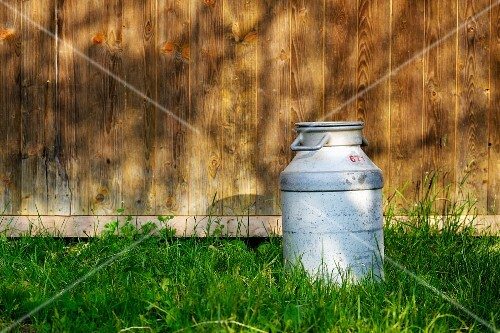 A milk churn in the grass outside a wooden cabin
