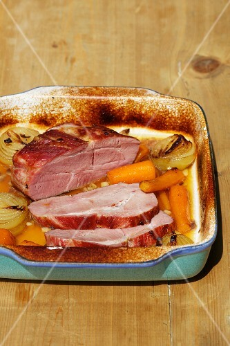 Roast ham with vegetables in the roasting tin