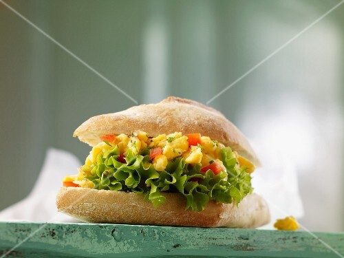 A baguette roll filled with scrambled egg, tomatoes and lettuce