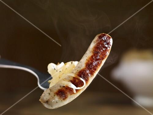 A steaming grilled bratwurst sausage with sauerkraut