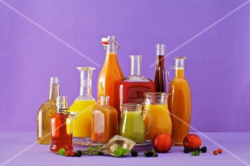 Freshly squeezed fruit juices in assorted glass containers against a purple background