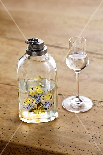 An old schnapps bottle and a glass of schnapps