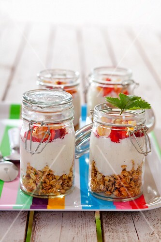 Four jars containing ingredients for muesli: rolled oats, vanilla yoghurt and strawberries