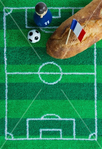 A baguette with a French flag and football-themed decoration