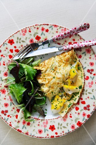An omelette with smoked fish and salad