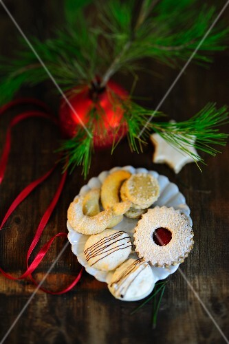 A plate of biscuits with vanilla crescents, German shortbread, coconut macaroons and a jam filled shortbread; a star-shaped cinnamon biscuit to one side