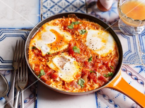 Huevos rancheros with tomatoes, with a glass of orange juice
