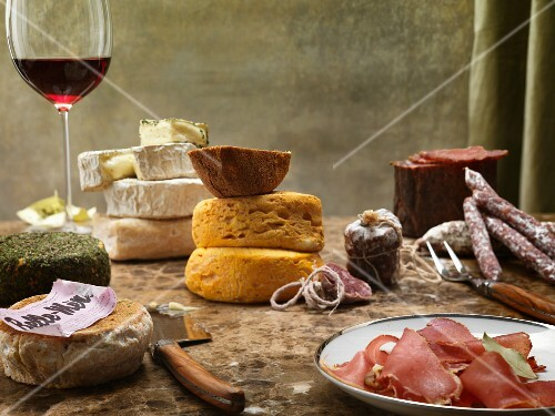 A still life featuring cheese, sausage and red wine from France