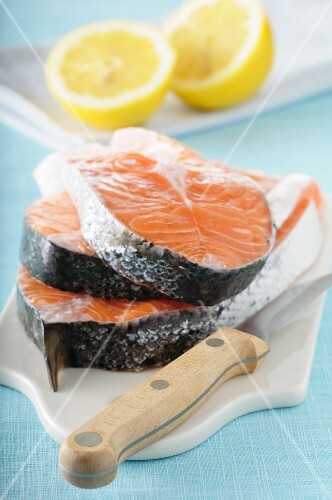 Three fresh salmon steaks on a chopping board
