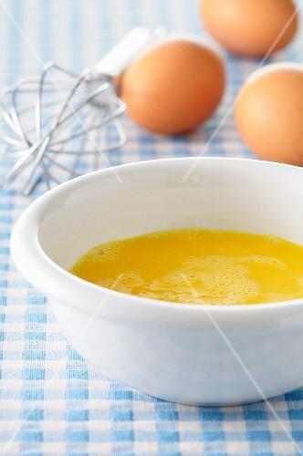 Beaten eggs in a porcelain dish