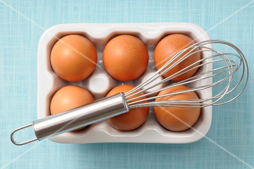 An egg whisk and six brown eggs in a porcelain egg box