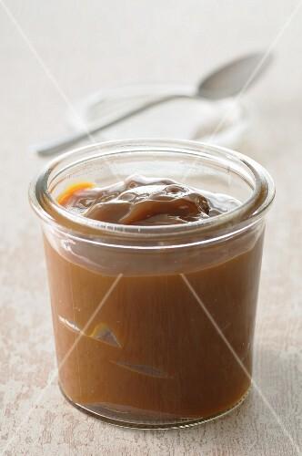 Caramel dessert in a glass pot