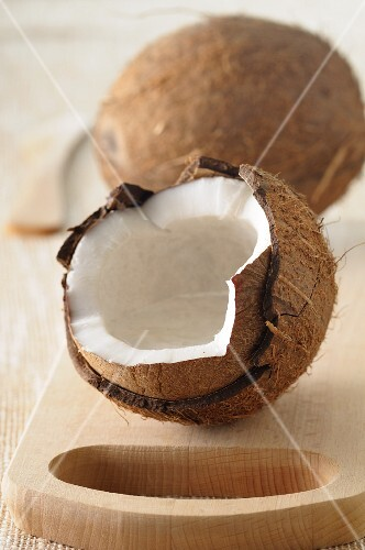 A whole coconut and one broken open, on a wooden board