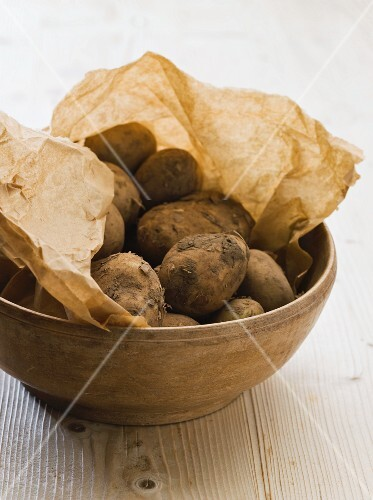 Fresh potatoes on brown paper in a bowl