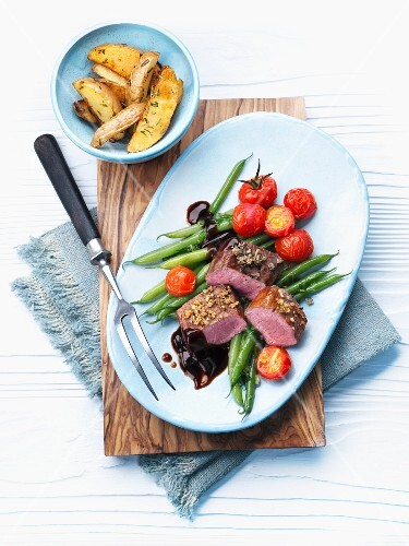 Lamb eye of loin with green beans, cherry tomatoes and roast potatoes