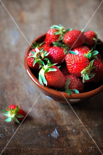 Fresh strawberries; a partly-eaten one to one side