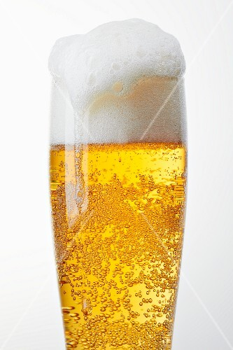 A glass of light beer with overflowing beer foam