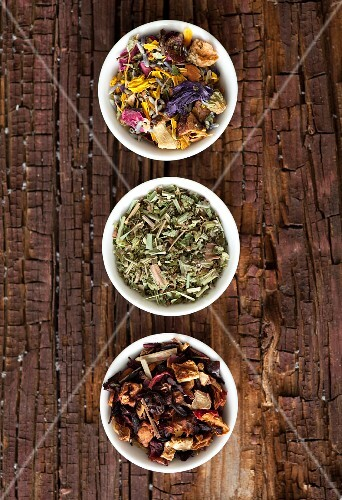 Assorted tea blends in small bowls on a rustic wooden surface