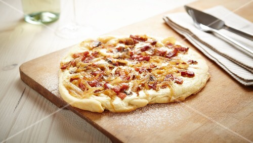 Tarte flambée topped with bacon and onions