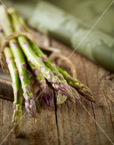 Green asparagus, bunched, on a wooden table
