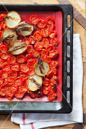 Roasted cherry tomatoes and onions in a baking tray