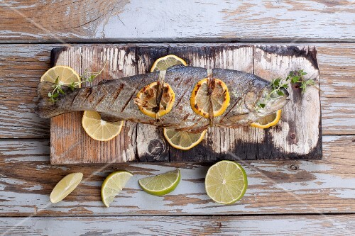 Barbecued trout with lemons and limes on a wooden board