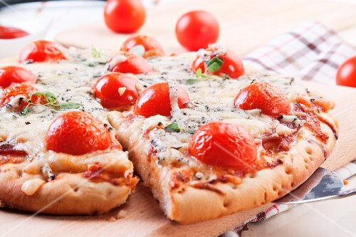 Pizza with blue cheese, ham and cherry tomatoes