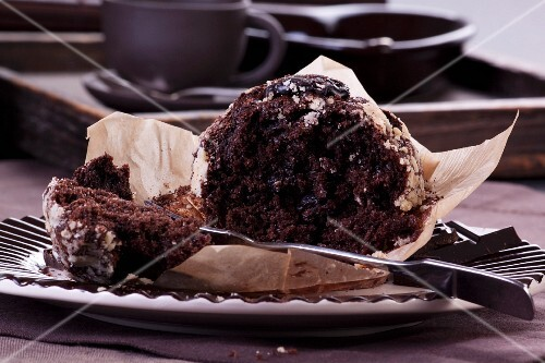 A chocolate muffin, partly eaten