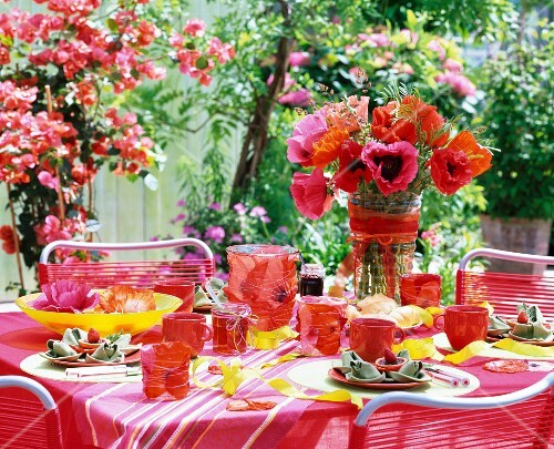 Summery table set with poppies in glass vases and a water bowl and hurricane candles with flower petals