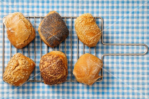Assorted bread rolls on a cooling rack