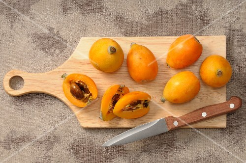 Medlars, whole and halved, on a chopping board